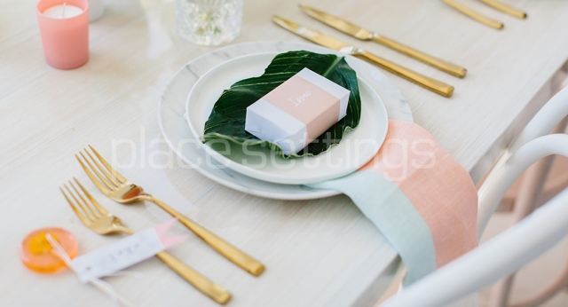 Table setting with white ceramic plates, gold cutlery and pinka dn white linen napkin