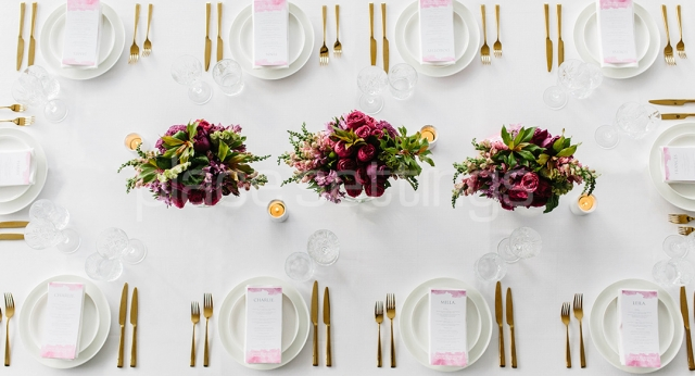 Table setting with white plates, tablecloth, gold cutlery and flowers
