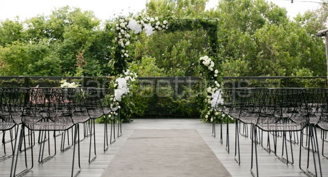 Outdoor Ceremony Setting with Black Wire Chairs and Green Floral Archway