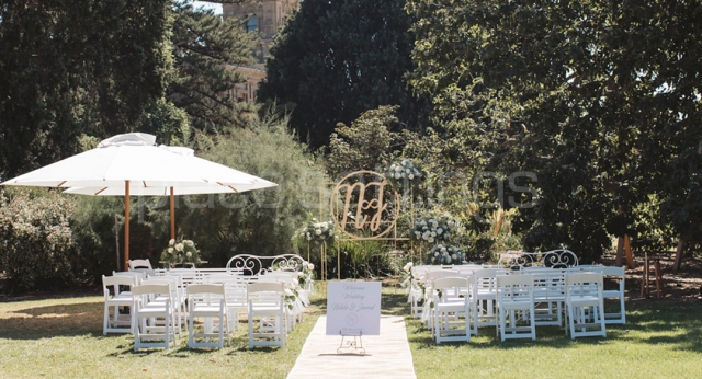 Outdoor Ceremony with White Chairs and Umbrellas
