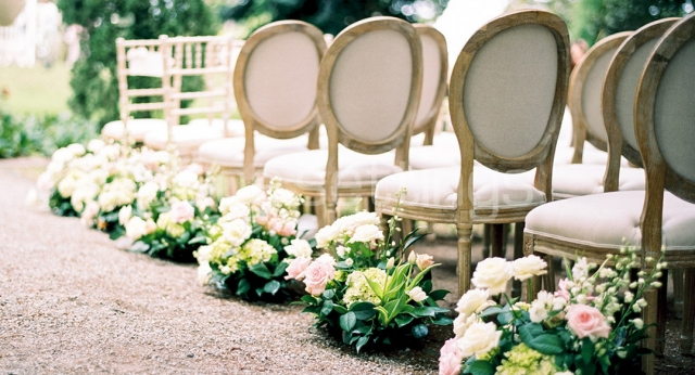 Wedding aisle with white fabric chairs and flower arrangements