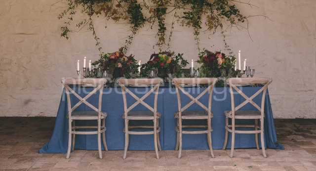 Rustic table setting with blue tablecloth, wooden chairs, candelabras and roses